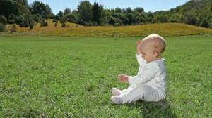 stock-footage-baby-sitting-on-green-lawn-and-picking-up-grass