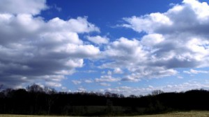 stock-footage-time-lapse-with-cloud-formations-moving-away-from-viewer-over-a-field-and-a-small-forrest-full-hd